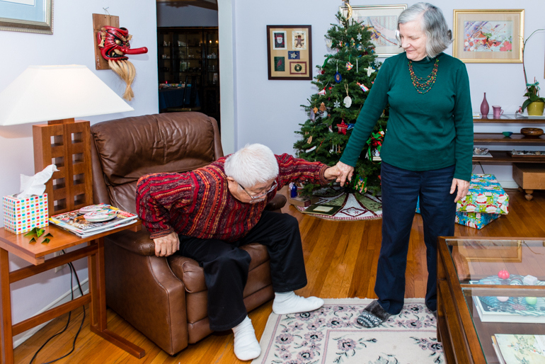 Diana Matsushima helps her husband Yoshi up from the recliner chair. After her husband suffered a stroke, Matsushima needs to help him get around. (Heidi de Marco/KHN).